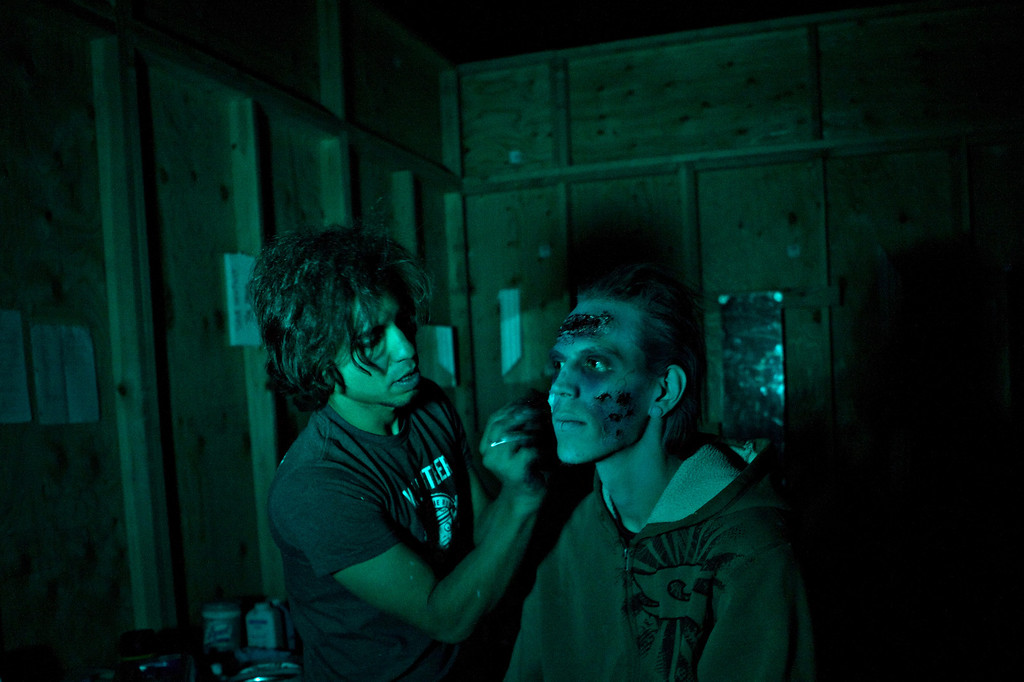 . Head makeup artist Kevon Ward finishes the makeup on actor Scott Grange after the lights had already gone off for the night to start at The Asylum Haunted House in Denver, Colorado, Saturday, October 19, 2013. Denver haunted houses The Asylum and the 13th Floor are both run by Screamworks Entertainment and have been recognized by MTV, The Travel Channel and USA Today as some of the best haunted houses in the country. (Photo By Katie Wood/The Denver Post)