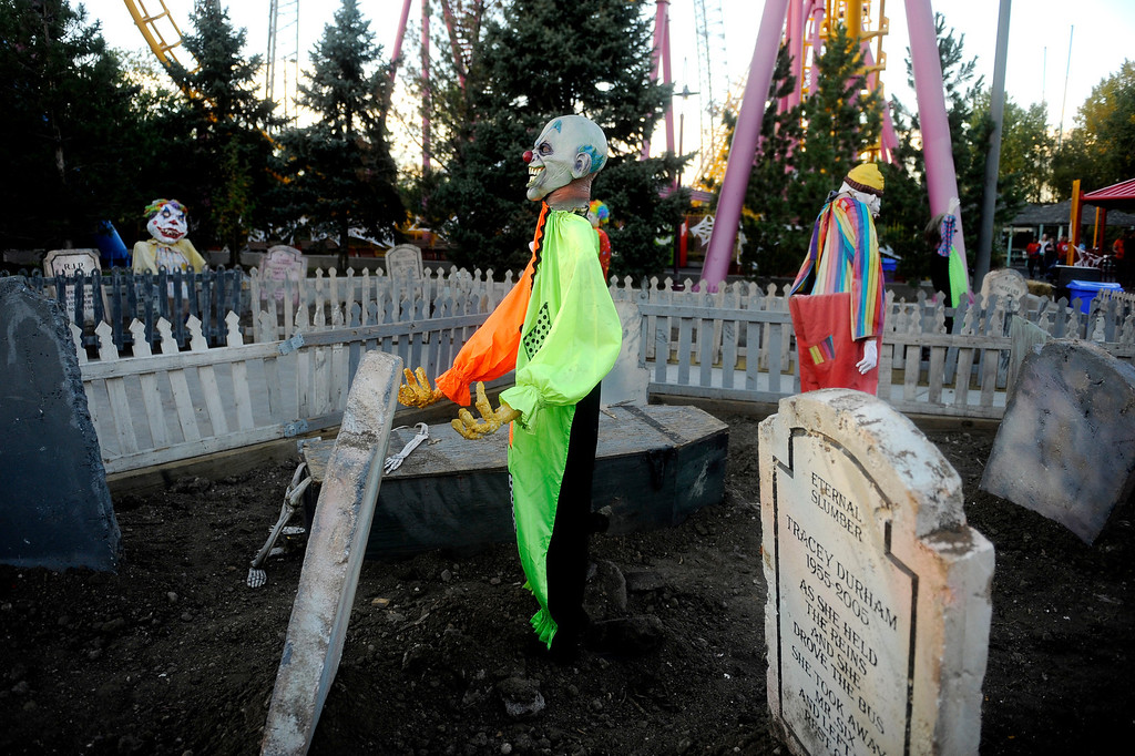 . Clowns stand in a graveyard at Fright Fest 2013 at Elitch Gardens. This is one of many Halloween displays throughout the park.  (Photo By Erin Hull/The Denver Post)