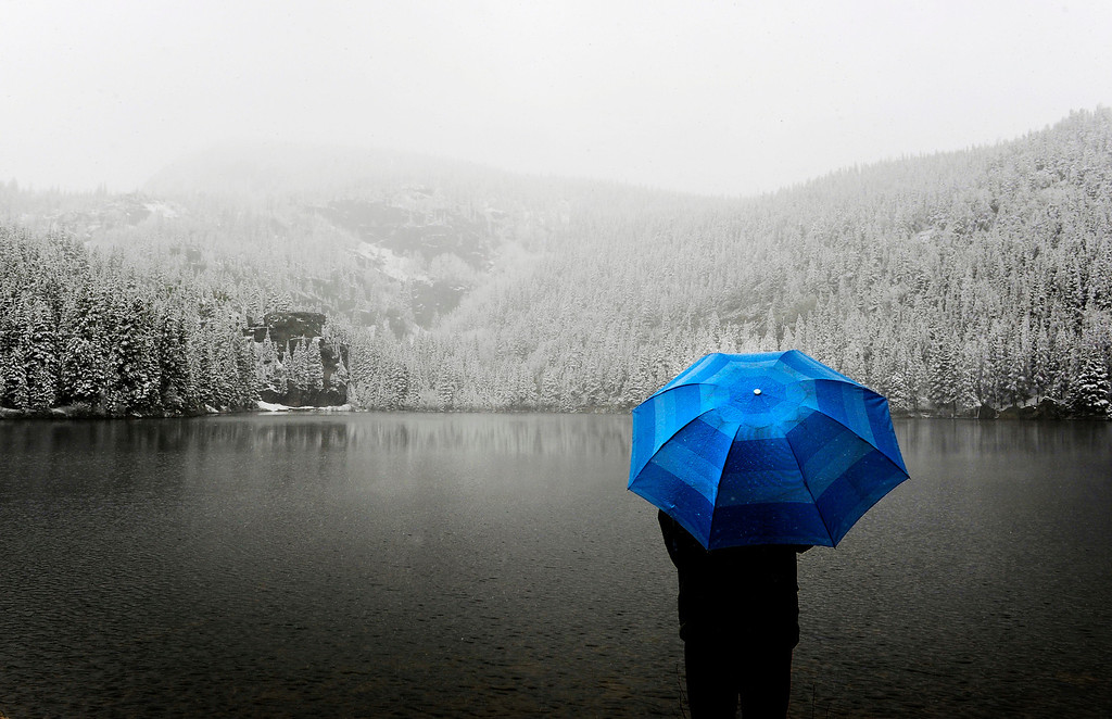 . Tan Wanwei, visiting from China, enjoys the view from Bear Lake at Rocky Mountain National Park as snow falls in the area on Monday, May, 07, 2012. The Colorado mountains are getting hit was a May snow storm. (Photo by RJ Sangosti/The Denver Post)