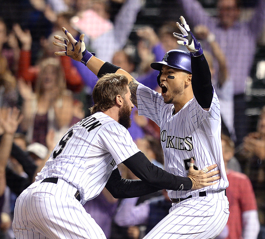 . DENVER, CO - MAY 20: Charlie Blackmon grabbed Carlos Gonzalez after he scored the winning run in the ninth inning. Colorado batter Nolan Arenado doubled to drive in two runs in the bottom of the ninth inning. The Colorado Rockies defeated the San Francisco Giants 5-4 at Coors Field Tuesday night, May 20, 2014. (Photo by Karl Gehring/The Denver Post)