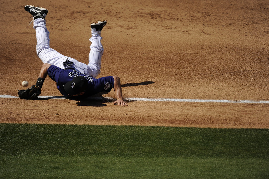 . Todd Helton knocks down a ground ball from Angel Pagan in the third inning during the Colorado Rockies home opener against the San Francisco Giants at Coors Field on April 9, 2012. AAron Ontiveroz, The Denver Post