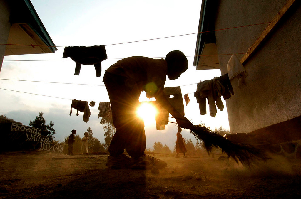 . Orphan Francis Luka, 11, gets an early start on chores sweeping the grounds as the sun rises in the morning around 6:00 am. Guardians and teachers assign chores each day for the children. Africa has 12.3 million  children orphaned by AIDS. The still-growing AIDS crisis claims about 6,300 African lives each day, 2.3 million a year and now more than 20 million and counting.  (Photo By Helen H. Richardson/The Denver Post)
