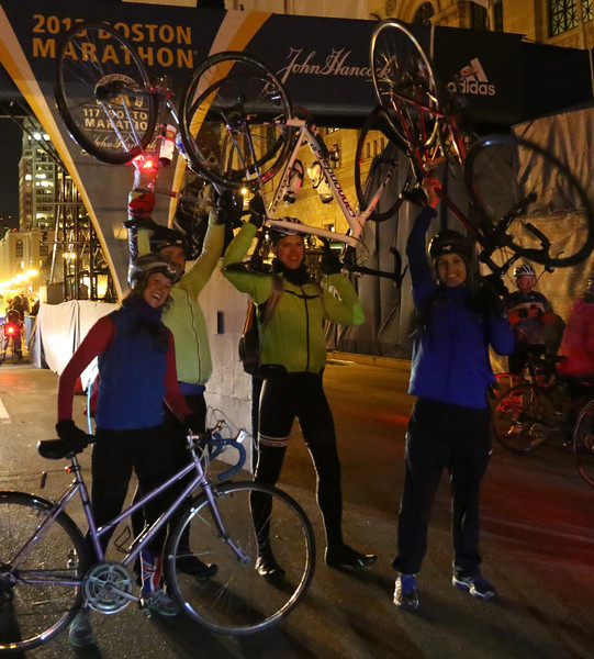 Boston, Mass. April 14- Cyclists triumphantly lift their bikes over their heads at the finish line of the Boston Marathon.  Over 700 cyclists participated in the annual Midnight Bike Marathon in Boston, the night before the running event.  Photo by Hannah Klarner/ Boston University News Service