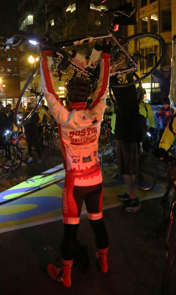 Boston, Mass. April 14- A member of the Boston University club cycling team lifts his bike overhead at the finish line of the Boston Marathon.  He was just one of over 700 participants in the Midnight Marathon Bike ride, where cyclists complete the Boston Marathon route the night before the race.  Photo by Hannah Klarner/ Boston University News Service