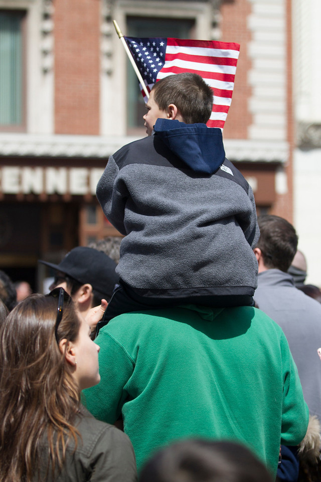 A young boy watches the Boston Marathon on Monday from an adult's shoulders. The crowds were thick near the finish line at Copley Square. (Photo by Micaela Bedell)