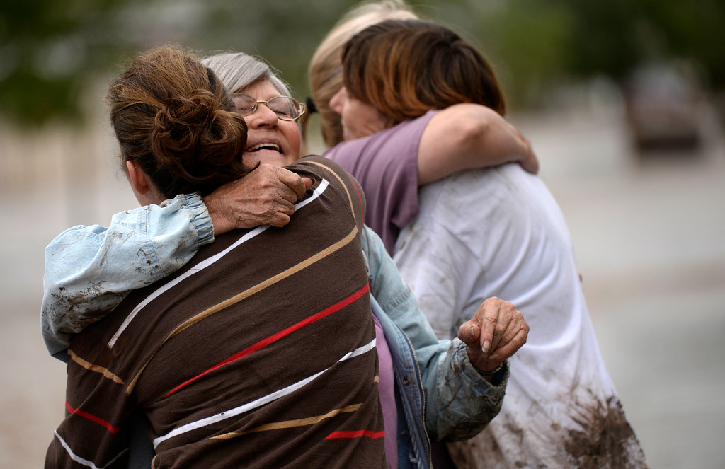 . EVANS, CO - SEPTEMBER 16: Virginia Tucker, second from the left, gets hugs from friends and family after getting to dry ground in Evans, September 16, 2013. Massive flooding continues to hit Colorado. (Photo By RJ Sangosti/The Denver Post)