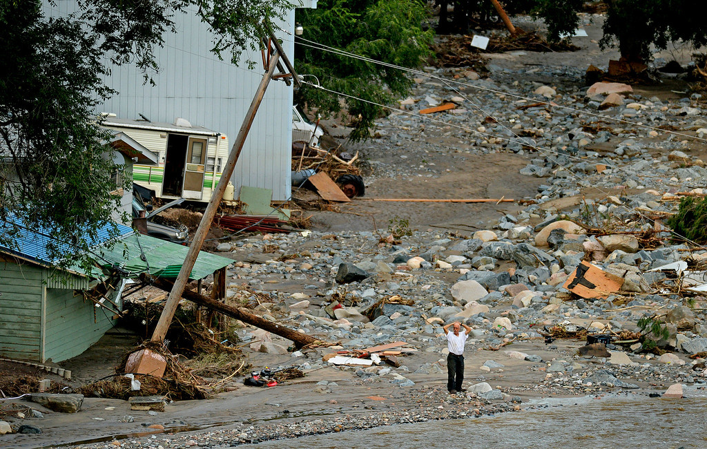 . Standing amid an enormous debris field near the mouth of Big Thompson Canyon, a man holds his head while watching the river. A stretch of 20 miles of U.S. 34 between Loveland and Estes Park was severely damaged by flooding.
