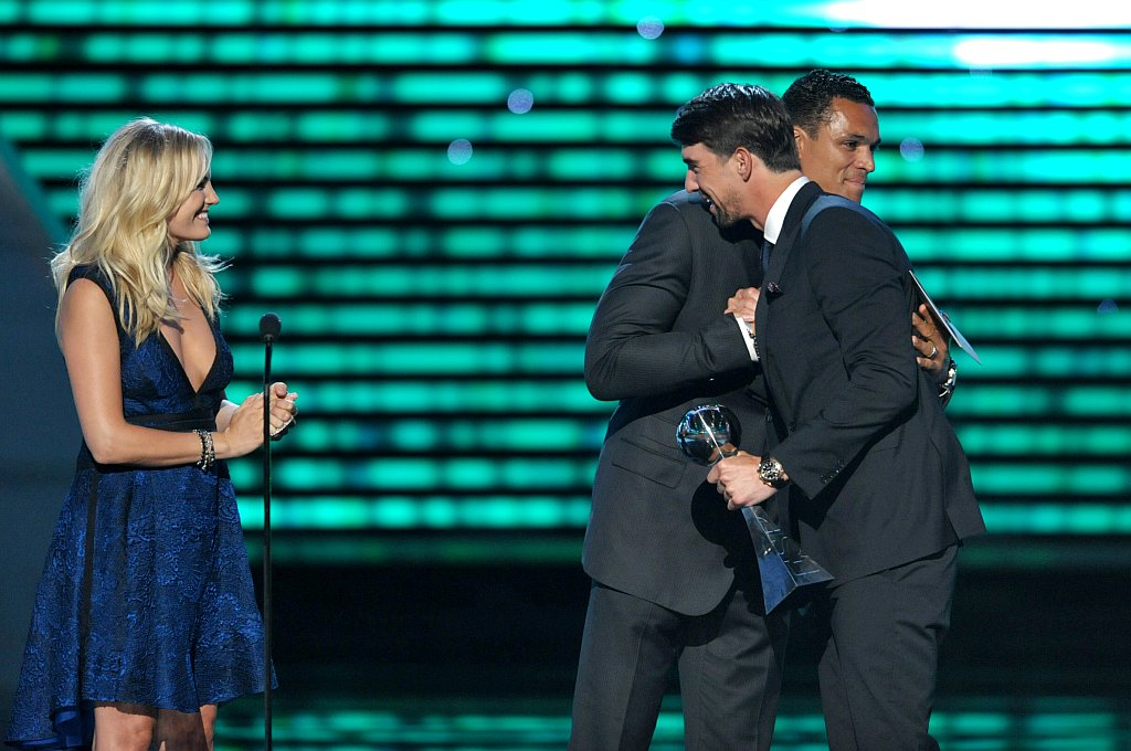 . From left, Malin Akerman and Tony Gonzalez present the award for best record-breaking performance to Michael Phelps at the ESPY Awards on Wednesday, July 17, 2013, at Nokia Theater in Los Angeles. (Photo by John Shearer/Invision/AP)