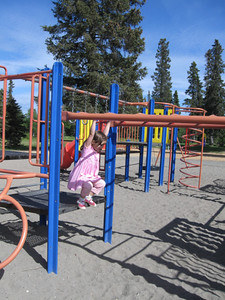Trying out the monkey bars at the Kenai City Park.  This was tough but she kept at it.