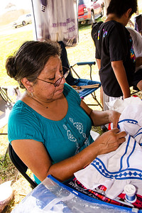 Debra Billy of Norman sews a Choctaw dress in the village.