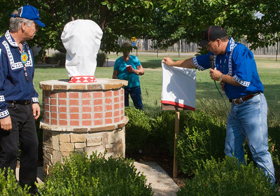 Assistant Chief Gary Batton removes the cover of the plaque beside the new bust of Charley Jones in the Capitol garden.