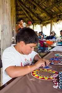 David Lankford, 13, of Tecumseh tries his hand at beading in the Choctaw village.