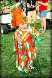 "Christian ""Lightning Boy"" Billy, 2, of Finley, plays his music before the pow wow grand entry on Friday night."