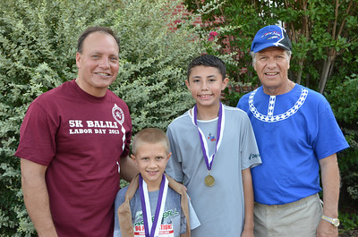 Second place Mason Mitchell and 1st place Isiah Marris in the 1-12 age bracket of the 5K with Assistant Chief and Chief.