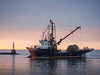 """Fishing boat """"Ocean Achiever"""" comes into Steveston Harbour at sunrise. Photo taken from Garry Point Park."""