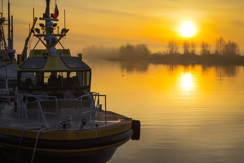"""Sunrise at Steveston Harbour with pilot boat """"Pacific Navigstor"""" in the foreground."""