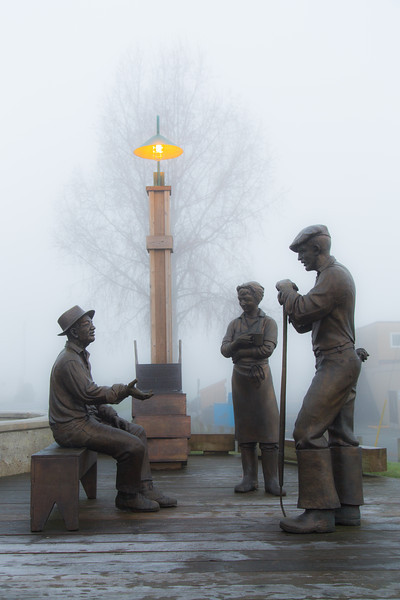 Steveston's Legacy sculpture in front of the Gulf of Georgia Cannery in Steveston on a foggy day.