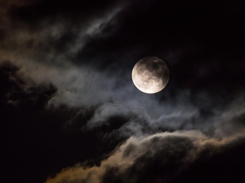 Snow moon behind clouds over Steveston.