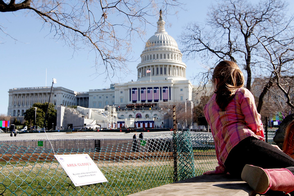 January 20, 2012 - A spectator looks on as preparations continue near the West Front of the Capitol building in Washington, D.C. on the day before the 57th Presidential Inauguration. Photo by Billie Weiss.