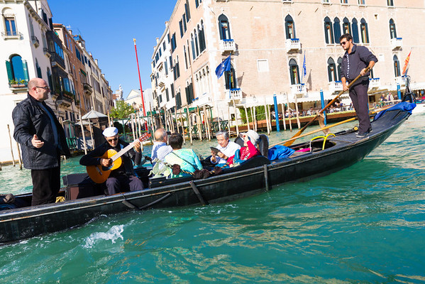 Guitarist, amplified speaker, and an Italian singer provide entertainment in addition to the sights and sounds of Venice.