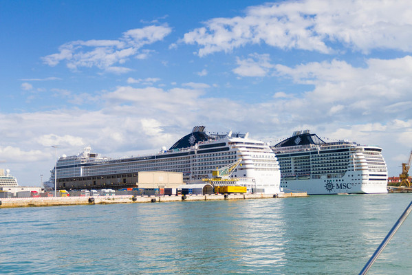 Two similar sized cruise ships are also docked nearby.
