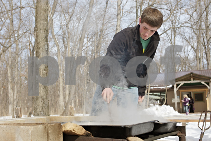 Rob Winner – rwinner@shawmedia.com<br /> <br /> Volunteer Alex Handel uses a wooden spoon to stir up three pans filled with boiling sap during Maple Syrup Fest in Genoa, Ill., Saturday, March 2, 2013. The heat from the fire evaporates the water which turns the sap into a syrup.