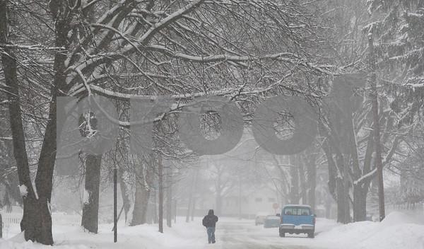 Kyle Bursaw – kbursaw@shawmedia.com<br /> <br /> A man walks down a snowy Fisk Avenue in DeKalb, Ill. on Tuesday, March 5, 2013.