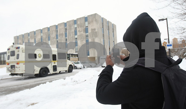 Kyle Bursaw — kbursaw@shawmedia.com<br /> <br /> A pedestrian stops to take a picture of the State Police command unit stationed outside the University Police and Public Safety building at Northern Illinois University in DeKalb, Ill. on Wednesday, March 6, 2013. The FBI and Illinois State Police served a search warrant at the building.