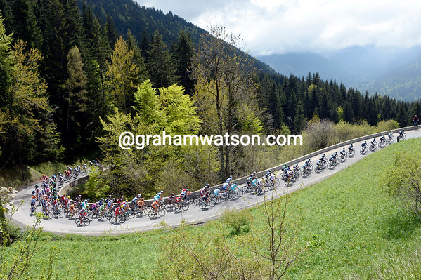 The strung-out peloton nears the summit of the green and glowing Col de Corbier...