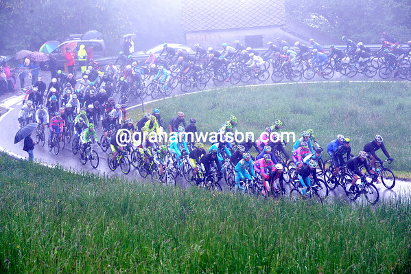 It's a wet and cold peloton that climbs the first hill...