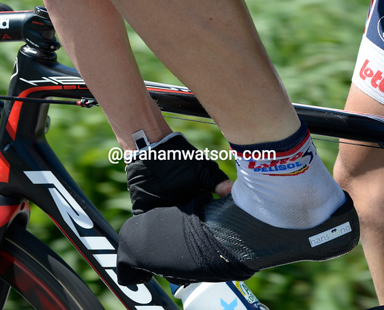 After four hours with no rain, Adam Hansen takes off his overshoes to reveal his tailor-made carbon shoes...