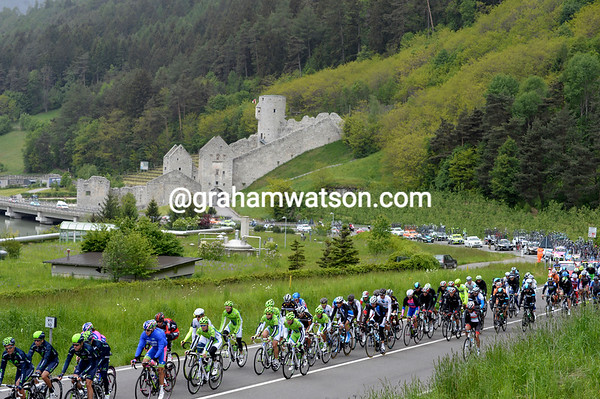 The peloton is well wrapped-up as it passes a deserted castle in Trentino...