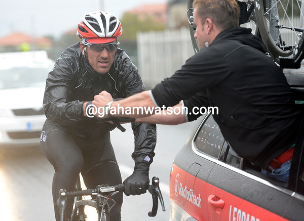 Fabian Cancellara is getting cold - he needs his mechanic's help to remove and swap his gloves...