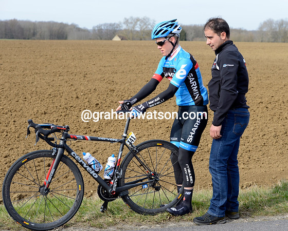Andrew Talansky tries to straighten his saddle - watched placidly by his Garmin mechanic...