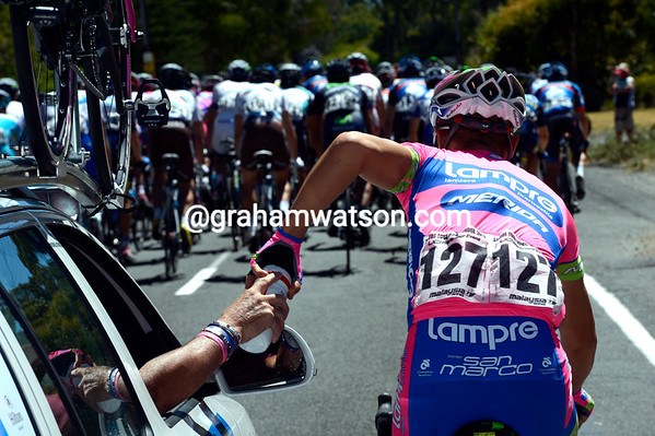 Simone Stortoni benefits from a slow-down at the front to grab some bottles fro Lampre...