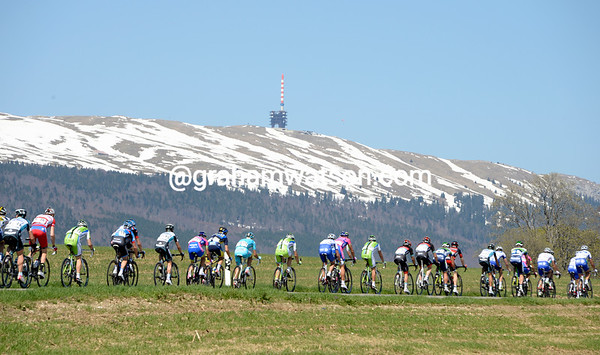 The skyline of the Vue des Montagnes dwarfs the strung-out peloton at the highest point of the day...