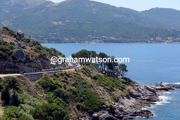 The Shack-led peloton passes a beautful bay on the east coast of Corsica...