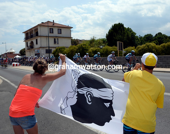 Some Corsican fans cheer the Tour along with the island's familiar flag...