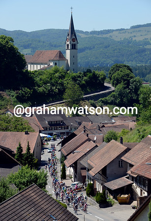 The peloton streams through a vilage during a fast start to the day...