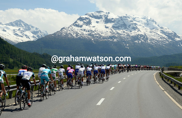 The peloton heads along the Engadin valley, surrounded by snowy peaks and illuminated by clear skies...