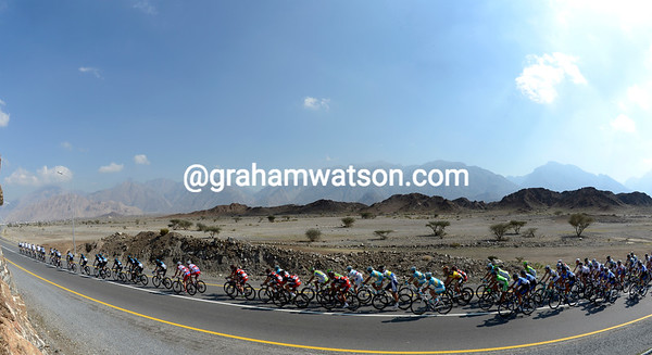 The peloton stretches out on a road surrounded by rocky mountains...