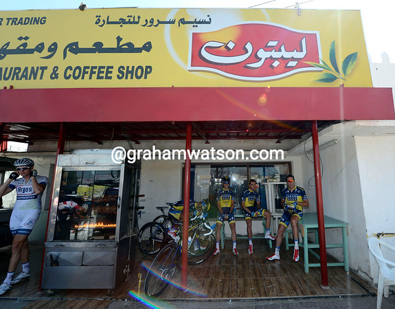 There are no smart buses for Saxo Bank cyclists to hide in, a coffee shop and seller of roasting chickens is their best shelter from the hot sun...