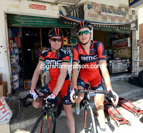 Cadel Evans and Taylor Phinney have managed to find shade outside a car-tire repair store...