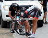 Fabian Cancellara does a quick stretch while his mechanic changes the rear wheel...