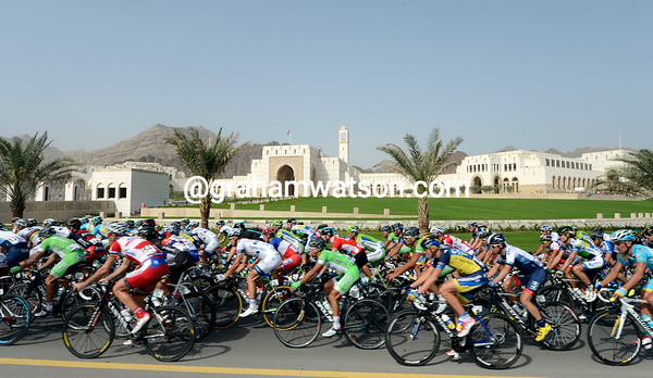 The peloton speeds past the new Parliament buildings in Al Bustan...