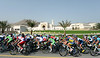 The peloton speeds past the new Parliament buildings in Al Bustan...