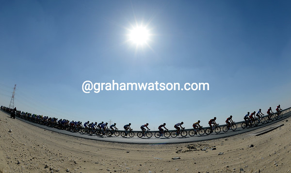 The peloton is led by BMC as it stretches across a desert landscape...