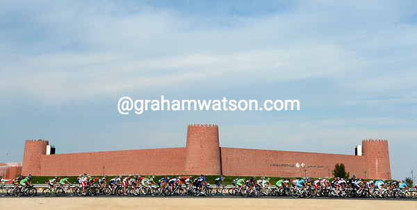 The peloton has regrouped as it passes a very modern fort at Al Shamal...