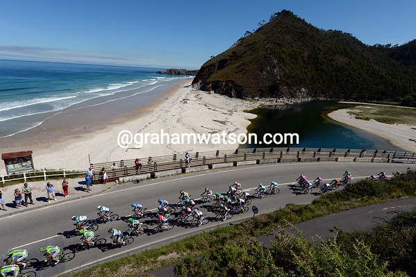 The peloton is at full stretch as it passes a beach on the Asturian coastline...