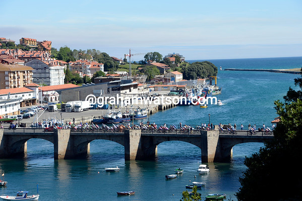 The peloton starts its day by crossing the old bridge in San Vicente de Baquera...